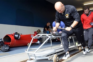A soldier pushes a modified bobsled.