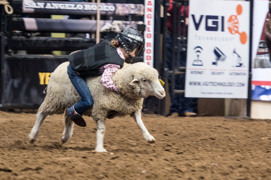 Neveah Wilmore, Goodfellow family member, participates in the mutton busting competition during Military Appreciation Night at the San Angelo Stock Show and Rodeo held at the Foster Communications Coliseum, Feb. 14, 2018, San Angelo, Texas. Mutton busting is an event where children ride race sheep and attempt to hold on for six seconds. (U.S. Air Force photo by Aryn Lockhart/Released)