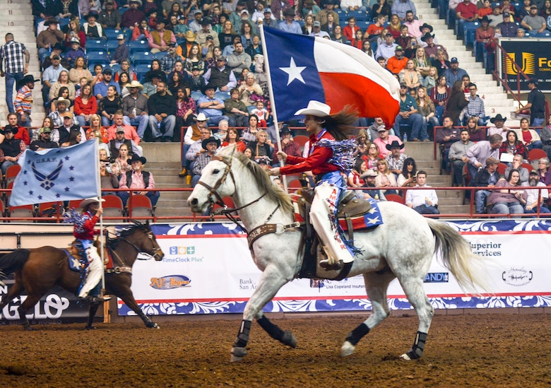 Members of the San Angelo Ambassadors ride through the arena with flags representing Texas and all of the military services during Military Appreciation Night at the San Angelo Stock Show and Rodeo at the Foster Communications Coliseum, Feb. 14, 2018, San Angelo, Texas. The Ambassador program is a rodeo drill team with 12 members who must be excellent riders and horse-women. (U.S. Air Force photo by Aryn Lockhart/Released)