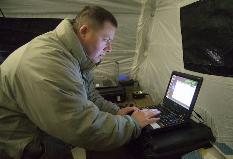 Tech. Sgt. Sean Newell, a radio frequency transmission systems technician, sets up a communication terminal during an aeromedical evacuation exercise Feb. 6, 2018, Scott Air Force Base, Illinois. The technicians use the terminal to access a secure website that allows for patient transport. He is with the 375th Communications Squadron but assigned to the 375th Aeromedical Evacuation Squadron as a member of the En-Route Patient Staging System team.  (U.S Air Force photo by Senior Airman Melissa Estevez)