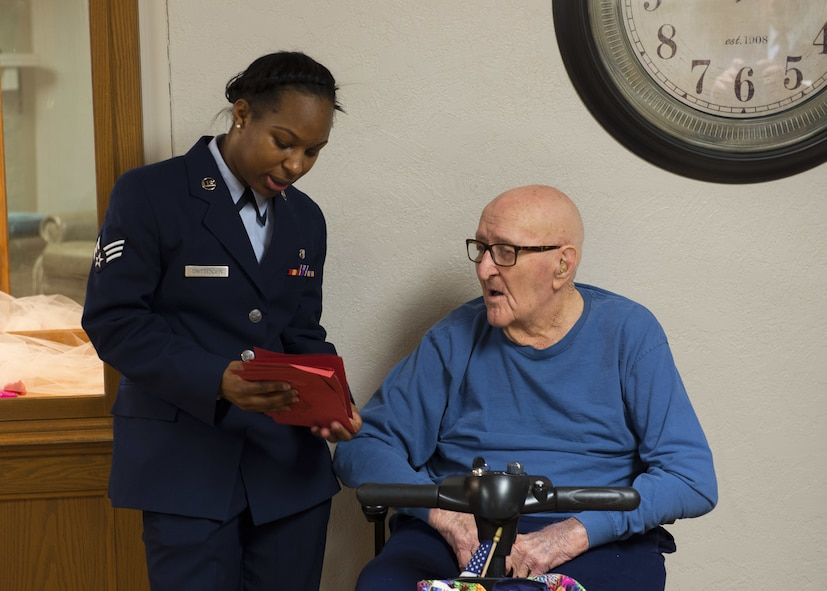 U.S. Air Force Senior Airman Valisia Crittenden, a dental assistant assigned to the 97th Medical Operations Squadron, reads a valentine to a veteran while volunteering for Valentines for Vets in English Village Manor, Feb. 14, 2018, in Altus, Okla.