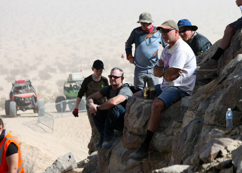 Spectators perch on a rock outcropping to watch a King of the Hammers attendees crawl up Back Door, Feb. 5, 2018. The challenging climb filled with rocks and deep craters is one of many that participants take on during KOH, the largest racing and rock-crawling event in North America. (Marine Corps photo by Kelly O'Sullivan)