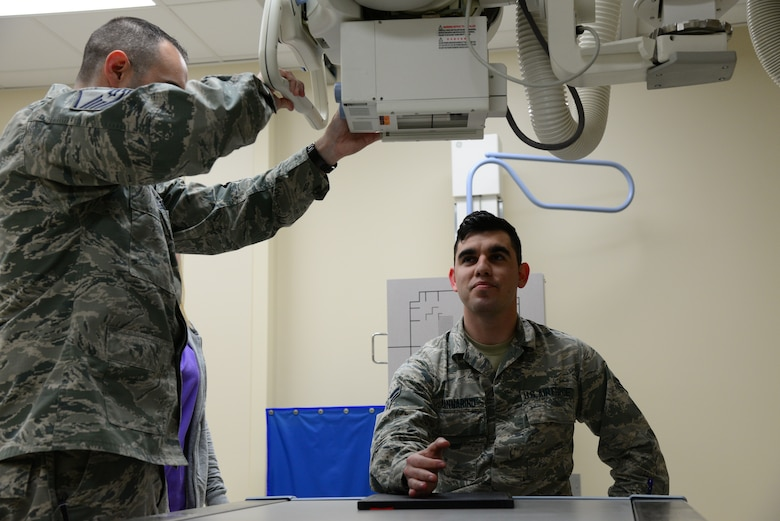 Airman 1st Class Michael Mannarino, 14th Medical Operations Squadron bioenvironmental engineer apprentice, simulates getting an X-ray Feb. 14, 2018, on Columbus Air Force Base, Mississippi. The X-ray machine works by taking 220 volts from the wall outlet and then amplify it to 100,000-140,000 volts by utilizing a transformer like machine. (U.S. Air Force photo by Airman 1st Class Beaux Hebert)