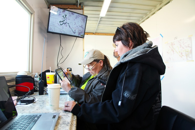 Katrina Symons, left, field manager, Bureau of Land Management Barstow, Calif., field office, and Kristina Becker, deputy director, Marine Corps Air Ground Combat Center Government and External Affairs, monitor the Can-Am KOH UTV Race in the King of the Hammers operations trailer in Johnson Valley, Calif., Feb. 7, 2018. Multiple federal, state and county agencies work together with race organizer HammerKing Productions during King of the Hammers, the largest off-road racing and rock-crawling event in North America. (Marine Corps photo by Kelly O'Sullivan)