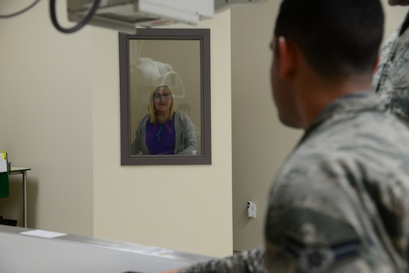 Torrie Gates, 14th Medical Support Squadron radiologic technologist, stands behind a wall while Airman 1st Class Michael Mannarino, 14th Medical Operations Squadron bioenvironmental engineer apprentice, simulates getting an X-ray Feb. 14, 2018, on Columbus Air Force Base, Mississippi. The Kortiz Clinic radiology department's primary mission is patient care which saves the Airmen time and trouble by getting quicker results. (U.S Air Force photo by Airman 1st Class Beaux Hebert)