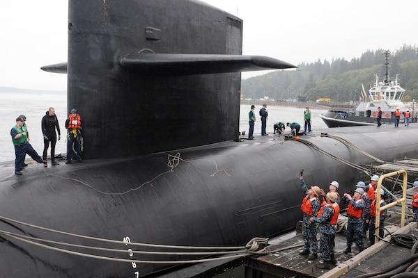 Sailors tie a submarine to a pier.