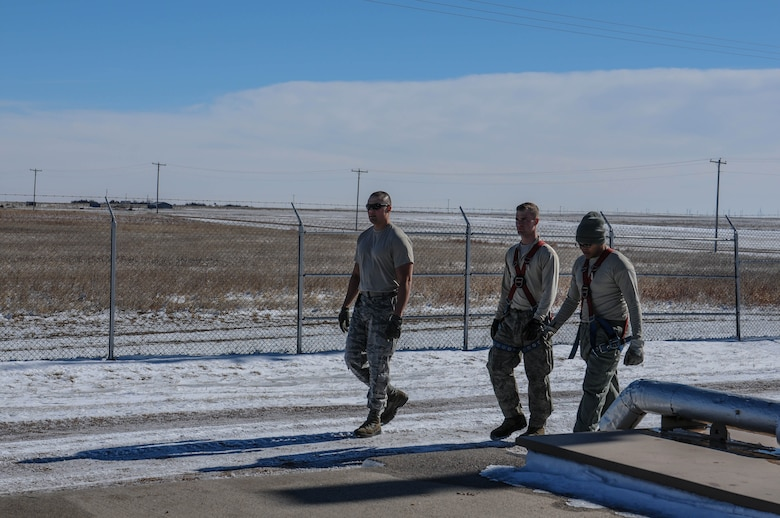 Airmen from the 90th Missile Maintenance Squadron walk onto a launch facility, Feb. 2, 2018, in the F.E. Warren Air Force Base missile complex. The 90th MMXS missile maintenance team earned the 2017 professional team of the year award for their constant professionalism in and out of the work place. Missile maintenance teams perform periodic maintenance to maintain the on-alert status for launch facilities, ensuring the success of the nuclear deterrence mission. (U.S. Air Force photo by Airman 1st Class Braydon Williams)