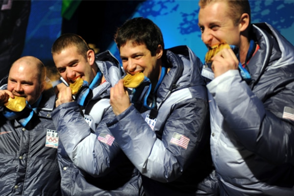 Former Army bobsledder Steven Holcomb and teammates Justin Olsen, middle left, Steve Mesler and Curt Tomasevicz bite their gold medals after winning the Olympic four-man bobsled crown during the 2010 Vancouver Olympic Games. Army photo by Tim Hipps