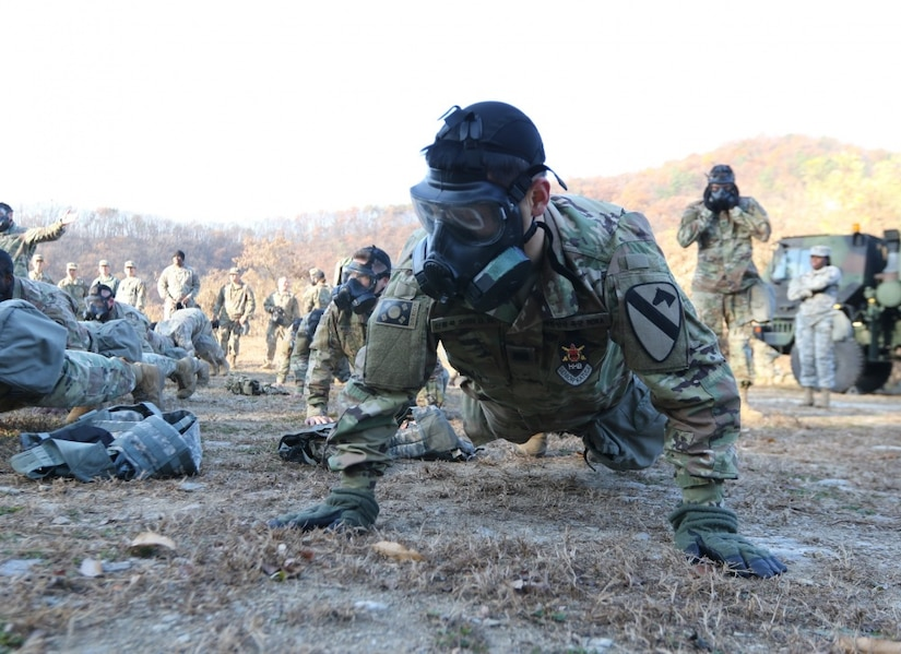 A soldier does pushups in a gas mask.