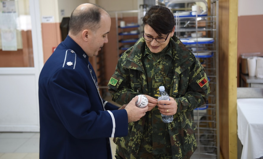 U.S. Air Forces in Europe Band commander, Lt. Col. Don Schofield, gives a souvenir baseball to a Kosovo Force soldier from Albania during a visit to Camp Film City, Kosovo, Feb. 15, 2018. The band visited Kosovo to celebrate the 10th anniversary of Kosovo independence. (U.S. Air Force photo by Maj. Tristan Hinderliter)