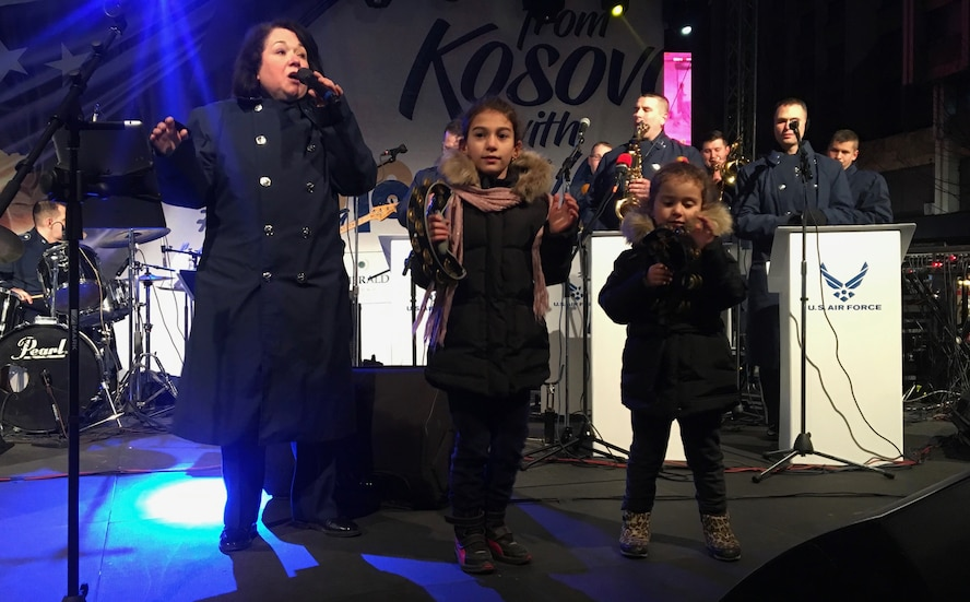 Two local girls join the U.S. Air Forces in Europe Band on stage during a show in Pristina, Kosovo, Feb. 15, 2018. The band visited and performed in Kosovo to celebrate the 10th anniversary of Kosovo independence. (U.S. Air Force photo by Maj. Tristan Hinderliter)