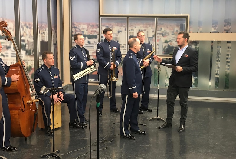 The U.S. Air Forces in Europe Band Commander, Lt. Col. Don Schofield, speaks to the Radio Television of Kosovo morning show host during a live broadcast in Pristina, Kosovo, Feb. 16, 2018. The band was in Kosovo to celebrate the 10th anniversary of Kosovo independence. (U.S. Air Force photo by Maj. Tristan Hinderliter)