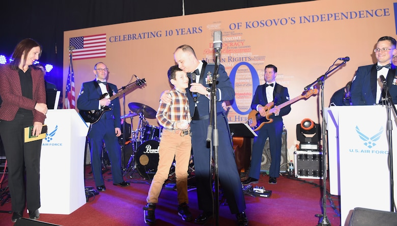 The U.S. Air Forces in Europe Band Commander, Lt. Col. Don Schofield, presents a souvenir baseball to a local child during a concert at Red Hall in Pristina celebrating the country's 10th anniversary of independence, Feb. 16, 2018. The event was hosted by the U.S. Ambassador to Kosovo, Greg Delawie, and broadcast live on Radio Television of Kosovo, the most-viewed television station in the country. The audience included diplomats, members of the Kosovo Security Forces and dozens of young Kosovars invited by the embassy. (U.S. Air Force photo by Maj. Tristan Hinderliter)