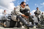 Hawaii Air National Guard Tech Sgt. Tashalynn Willing, a 154th Security Forces Squadron fire team member, puts on personal protective equipment during the Patriot South exercise at Camp Shelby, Miss.