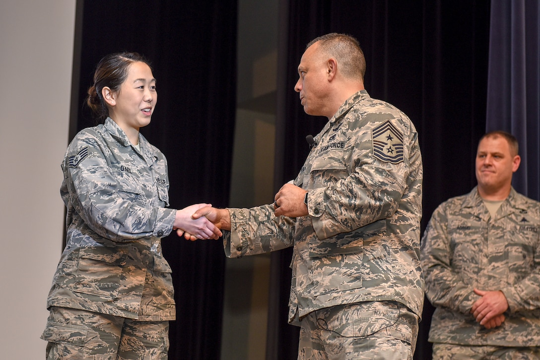 Chief Master Sgt. Matthew Caruso, command senior enlisted leader of U.S. Transportation Command, coins Staff Sgt. Heidi O'Neil, 4th Aircraft Maintenance Squadron personnel technician, for her outstanding performance during a senior NCO all call at the theater Feb. 15, 2018, at Seymour Johnson Air Force Base, North Carolina.