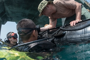 Navy Petty Officer 1st Class Matt Ramirez, a construction mechanic assigned to Underwater Construction Team 2, checks the bottle pressures for Navy Seaman Recruit Adam Porras and a Thai sailor during a dive at Thung Prong Pier in Sattahip, Thailand.