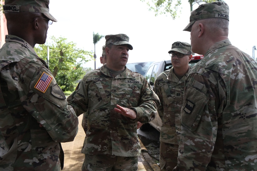 Brig. Gen. Hector Lopez, commanding general of the 94th Training Division, discusses some of the devastating impact of Hurricane Maria with Maj. Gen. Bruce Hackett, commanding general of the 80th Training Command (TASS) on 14 Feb 2018 as they tour severely damaged former training facilities in Puerto Rico. Maj. Gen. Hackett and Brig. Gen. Lopez were at Fort Buchanan to celebrate the reopening and relocation of a schoolhouse for the 94th Training Division's 5th Battalion. They were also on the island to assist with the planned tranistion and approved reassignment of all units stationed in Puerto Rico to the operational control of the 1st Mission Support Command.  Photo by Army Master Sgt. Benari Poulten, 80th Training Command (TASS) Public Affairs