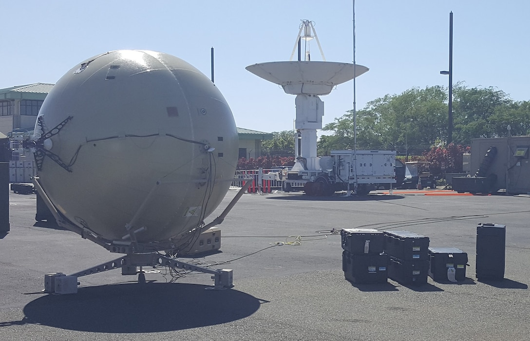 With support from the Air Force Small Business Innovation Research/Small Business Technology Transfer Program, GATR Technologies developed a portable antenna with tracking capability. Shown here (in the foreground), the GATR TRAC packs into cases that are easy to transport compared to traditional antenna systems such as the one shown in the background. (Photo courtesy of GATR Technologies)