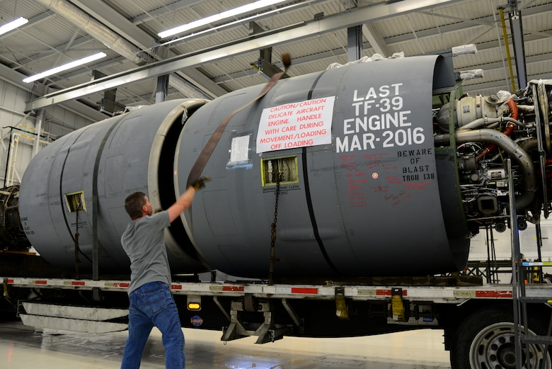 Wesley Currin, Triple J Trucking driver, throws a tie-down strap over a General Electric TF-39 turbofan engine Feb. 16, 2018, at Dover Air Force Base, Del. The North Carolina native drove the Air Force's last functional TF-39 engine to Monroe, N.C., where it was purchased by a metals reclamation company. (U.S. Air Force photo by Staff Sgt. Aaron J. Jenne)