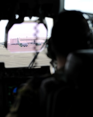 A rectangle photo with a male looking out an aircraft windshield at an aircraft.