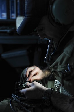 A rectangle photo with a male in a dark aircraft cockpit leaning over a cord making repairs.
