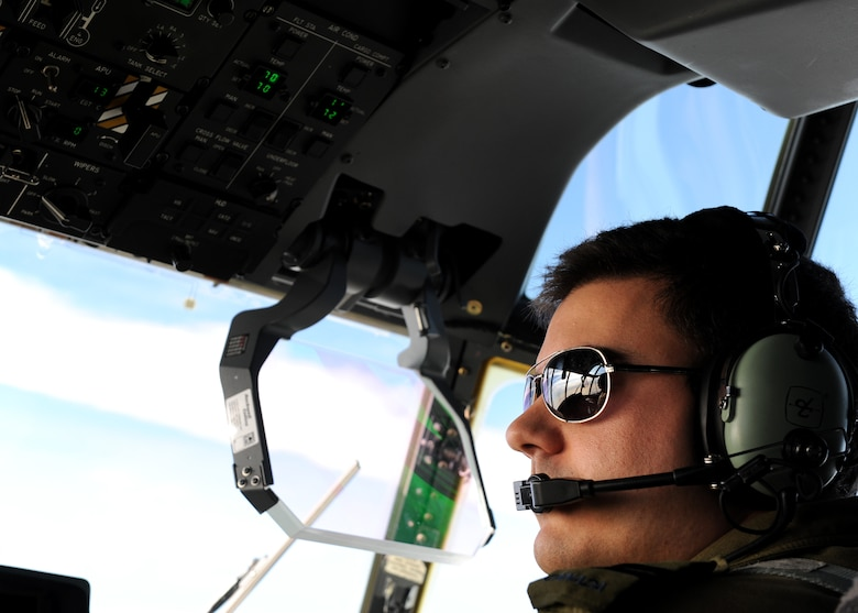 A square photo with a male wearing a headset looking out an aircraft windshield.