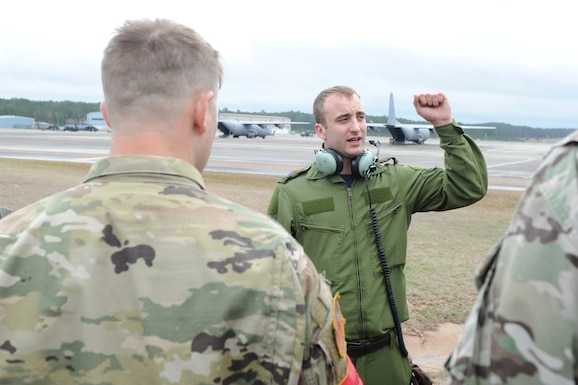 A rectangle photo with males in uniform in front of a flightline with aircraft.