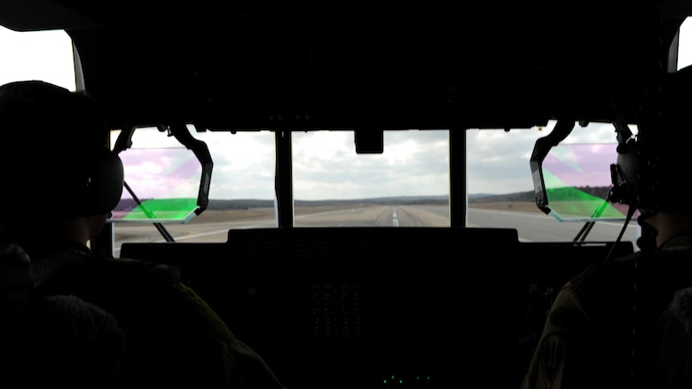 A rectangle photo with two silhouettes in front of an aircraft windshield.