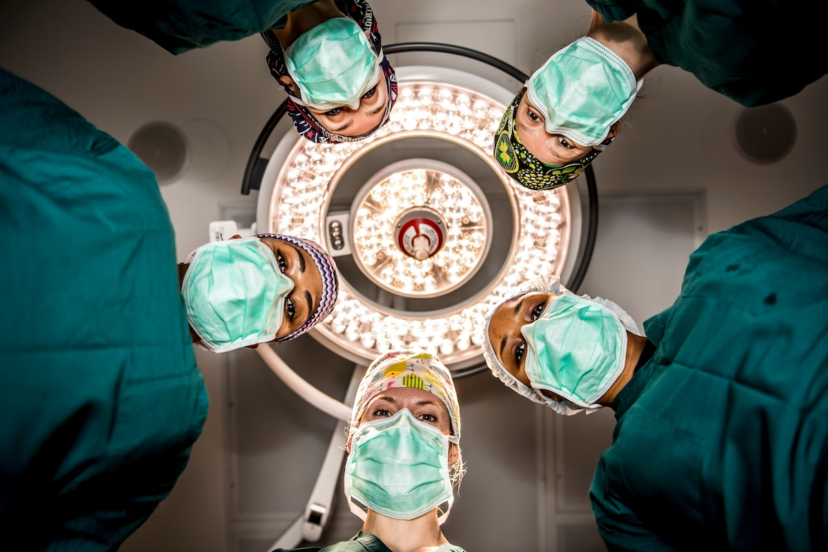 Five felmale surgeons look down at a camera.