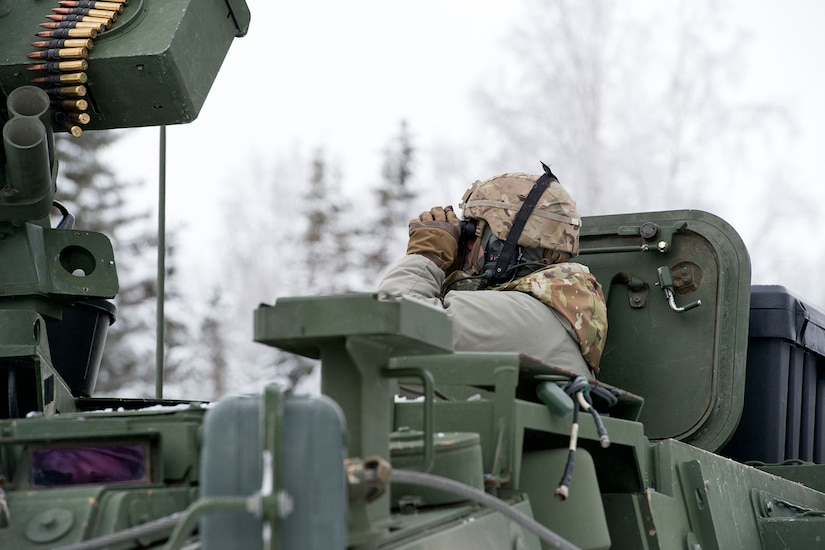 A Soldier assigned to Bayonet Company, 1st Battalion, 5th Infantry Regiment, 1st Stryker Brigade Combat Team, 25th Infantry Division, U.S. Army Alaska, surveys the surrounding area while preparing for live-fire gunnery training during Operation Punchbowl at Joint Base Elmendorf-Richardson, Alaska, Feb. 16, 2018. Operation Punchbowl was a battalion-level, combined arms, live-fire exercise that focused on arctic lethality.