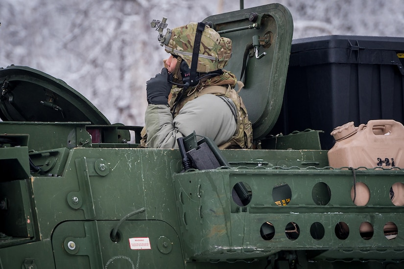 Army 1st Lt. Daniel Choi, a vehicle commander assigned to Bayonet Company, 1st Battalion, 5th Infantry Regiment, 1st Stryker Brigade Combat Team, 25th Infantry Division, U.S. Army Alaska, communicates with his crew as they prepare to maneuver onto the range for gunnery on Joint Base Elmendorf-Richardson, Alaska, during Operation Punch Bowl. The Fort Wainwright based Soldiers' operation culminated with multiple live-fire and combat training events.