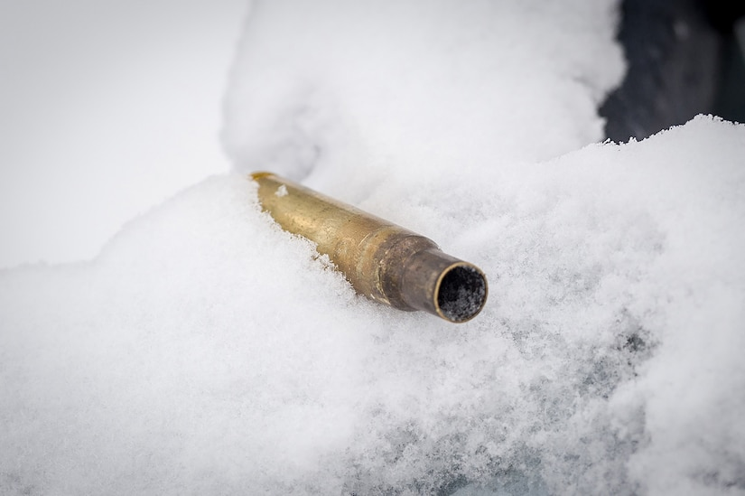 An expended .50 caliber machine gun casing is seen embeded in the snow as Soldiers assigned to the 1st Battalion, 5th Infantry Regiment, 1st Stryker Brigade Combat Team, 25th Infantry Division, U.S. Army Alaska, execute gunnery on Joint Base Elmendorf-Richardson, Alaska, during Operation Punch Bowl. The Fort Wainwright based Soldiers' operation culminated with multiple live-fire and combat training events.