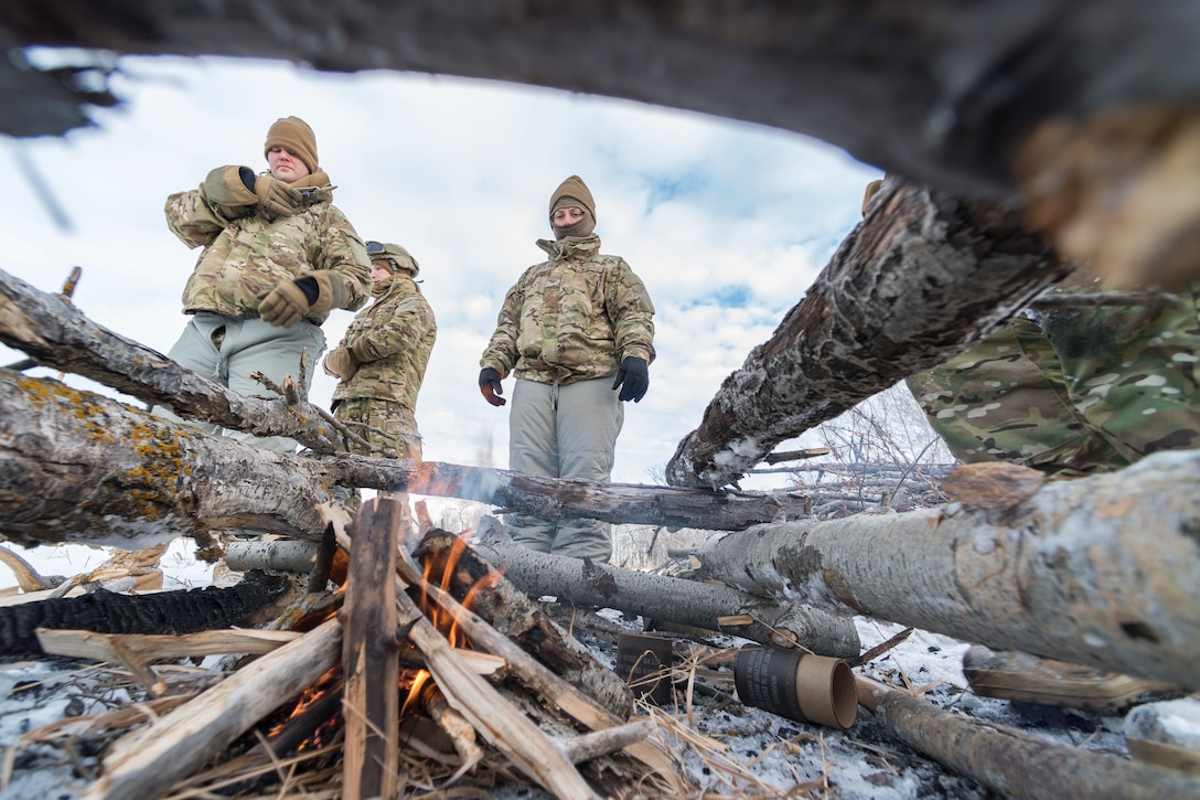 Defenders from the 91st Security Forces Group stand near a fire during a field training exercise in the Turtle Mountain State Forest, N.D., Feb. 14, 2018. After navigating to a landing zone, Airmen created a signal fire by adding grass to the burning brushwood. (U.S. Air Force photo by Senior Airman J.T. Armstrong)