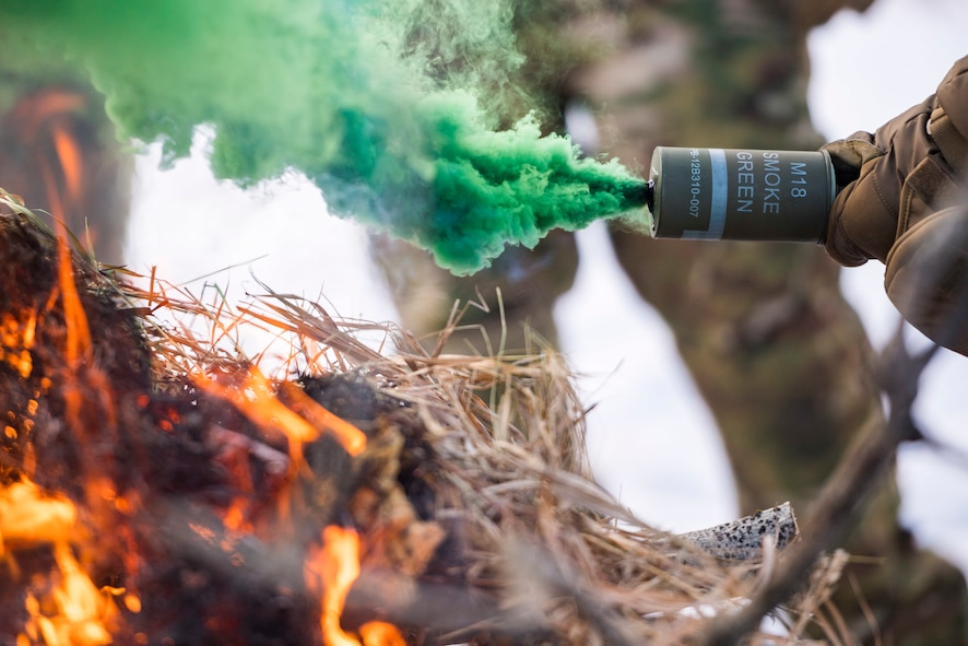 A 91st Missile Security Forces Squadron defender holds a M18 smoke grenade over a signal fire in the Turtle Mountain State Forest, N.D., Feb. 14, 2018. The signal fire's heat lifts the M18's green smoke for better signaling. (U.S. Air Force photo by Senior Airman J.T. Armstrong)