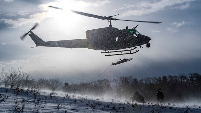 A UH-1N Iroquois assigned to the 54th Helicopter Squadron  lifts a simulated casualty above the Turtle Mountain State Forest, N.D., Feb. 14, 2018, during a 91st Security Forces Group field training exercise. During the FTX, defenders vectored the aircraft to a landing zone and performed a simulated medical evacuation. (U.S. Air Force photo by Senior Airman J.T. Armstrong)