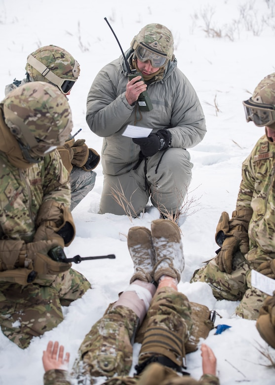 Members of the 91st Security Forces Group perform self-aid buddy care on a simulated casualty in the Turtle Mountain State Forest, N.D., Feb. 14, 2018. After stabilizing the casualty, defenders vectored in a rescue helicopter for an emergency medical evacuation. (U.S. Air Force photo by Senior Airman J.T. Armstrong)