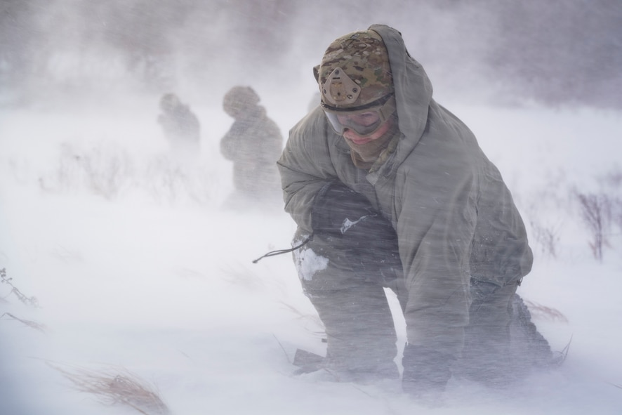 Staff Sgt. Benjamin Reynolds, 891st Missile Security Forces Squadron response force leader, crouches in rotor wash inside the Turtle Mountain State Forest, N.D., Feb. 14, 2018, during a field training exercise. During the exercise, 91st Security Forces Group defenders coordinated simulated medical evacuations with two 54th Helicopter Squadron UH-1N Iroquois. (U.S. Air Force photo by Senior Airman J.T. Armstrong)