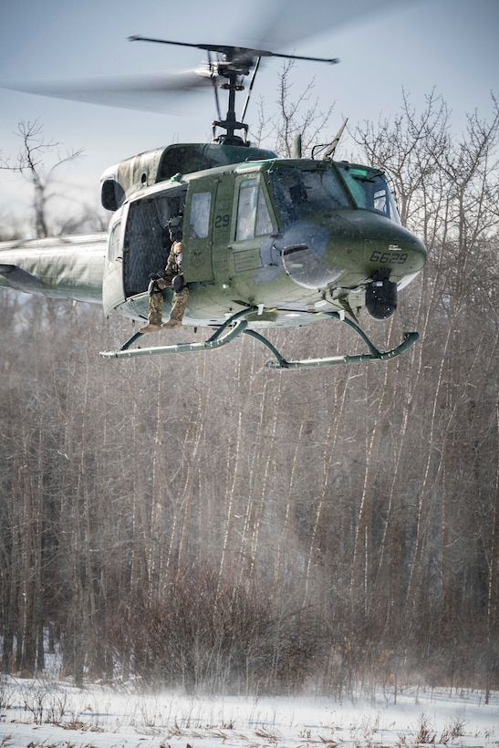 A 54th Helicopter Squadron UH-1N Iroquois hovers over the Turtle Mountain State Forest, N.D., Feb. 14, 2018, during a 91st Security Forces Group field training exercise. During the FTX, defenders vectored the aircraft to a landing zone and performed a simulated medical evacuation. (U.S. Air Force photo by Senior Airman J.T. Armstrong)