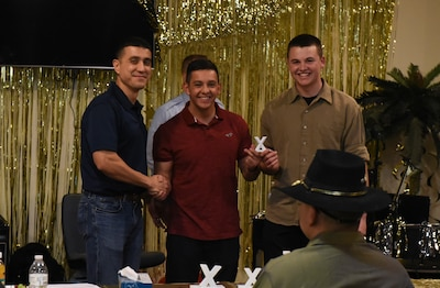 U.S. Air Force Col. Ricky Mills, 17th Training Wing commander awards Airman Ryan Marquez, 312th Training Squadron trainee, and Airman Dalton Neff, 312th TRS trainee, with the 3rd place trophy during the 11th Annual Talent Show at the Crossroads on Goodfellow Air Force Base, Texas, Feb. 16, 2018. Marquez and Neff played the guitar and kahan to the song 'You and Me' by Lifehouse. (U.S. Air Force Photo by Airman 1st Class Zachary Chapman/Released)
