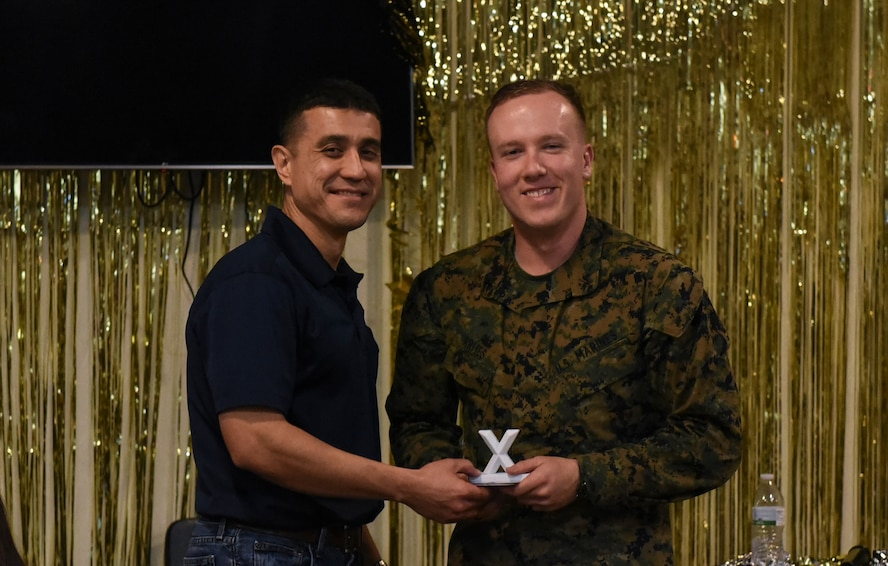 U.S. Air Force Col. Ricky Mills, 17th Training Wing commander, awards U.S. Marine Corps. Pfc. Jared Armes, Marine Corps Detachment trainee, with the 2nd place trophy during the 11th Annual Talent Show at the Crossroads on Goodfellow Air Force Base, Texas, Feb. 16, 2018. Armes played guitar and sang to an original song called 'Wayside'. (U.S. Air Force Photo by Airman 1st Class Zachary Chapman/Released)