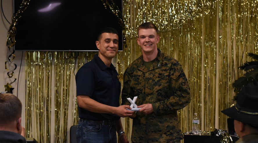 U.S. Air Force Col. Ricky Mills, 17th Training Wing commander, awards U.S. Marine Corps. Pfc. Connor Morgan, Marine Corps Detachment trainee, the 1st place trophy during the 11th Annual Talent Show at the Crossroads on Goodfellow Air Force Base, Texas, Feb. 16, 2018. Morgan received a standing ovation for his guitar solo that won him the 1st place spot. (U.S. Air Force Photo by Airman 1st Class Zachary Chapman/Released)