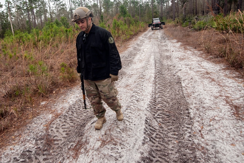 Staff Sgt. Michael Triana, 347th Operations Support Squadron independent duty mechanical technician, inspects the ground for footprints during combat survival training (CST), Feb. 13, 2018, at Moody Air Force base, Ga. CST prepares Airmen to avoid an enemy in the case that their aircraft were to crash in hostile territory.