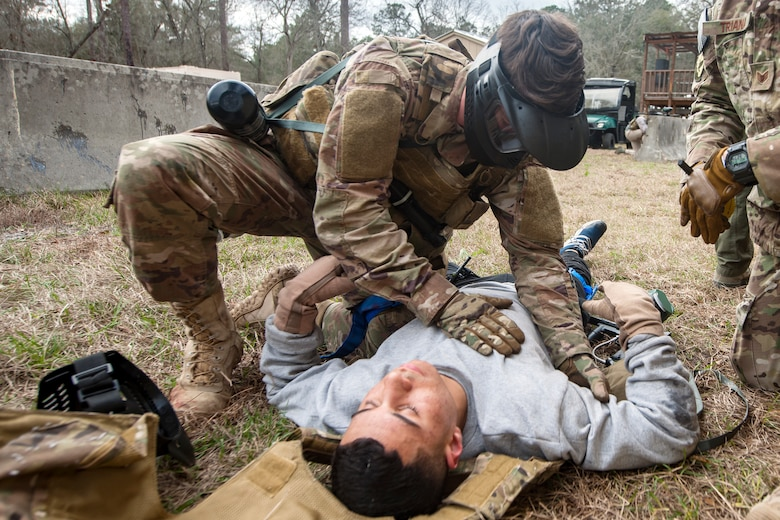 Airman 1st Class Elijah Bishop, 347th Operations Support Squadron intelligence analyst, top, examines Airman 1st Class Andruw Reyes, 23d Maintenance Squadron non-destructive inspection apprentice, Feb. 14, 2018, at Moody Air Force Base, Ga.  Airmen participated in a Tactical Combat Casualty Care (TCCC) course to better prepare themselves to combat an enemy attack while still being able to apply medical care under enemy fire.