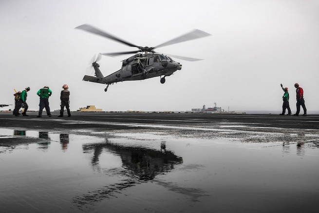 A Seahawk helicopter prepares to land on a ship's flight deck.