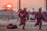 Two soldiers run during an event to earn an expert badge as the sun glows from the horizon.