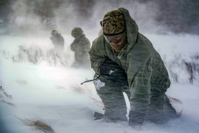 An airman crouches in rotor wash during an exercise.