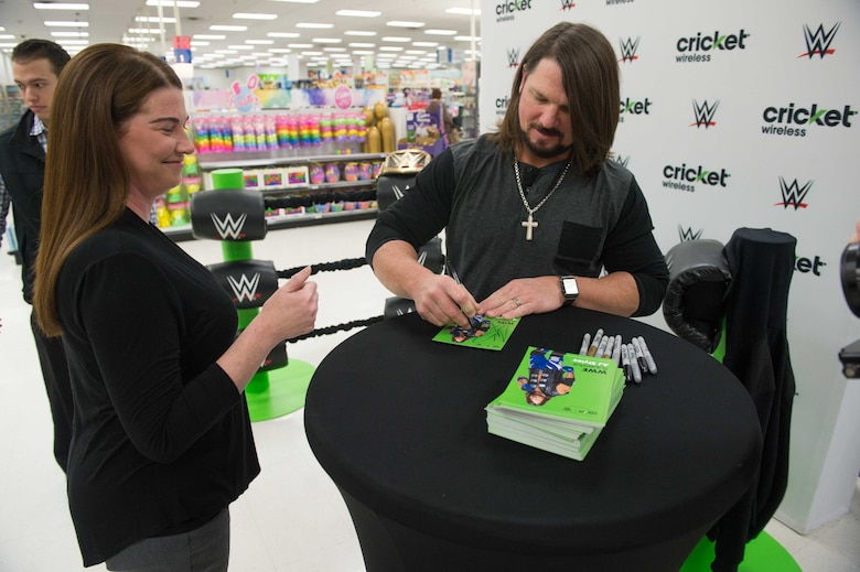 AJ Styles, World Wrestling Entertainment professional athlete, autographs a card for a fan at Luke Air Force Base, Ariz., Feb. 20, 2018. Airmen brought various items and memorabilia for Styles to autograph during the meet-and-greet event. (U.S. Air Force photo/Airman 1st Class Caleb Worpel)