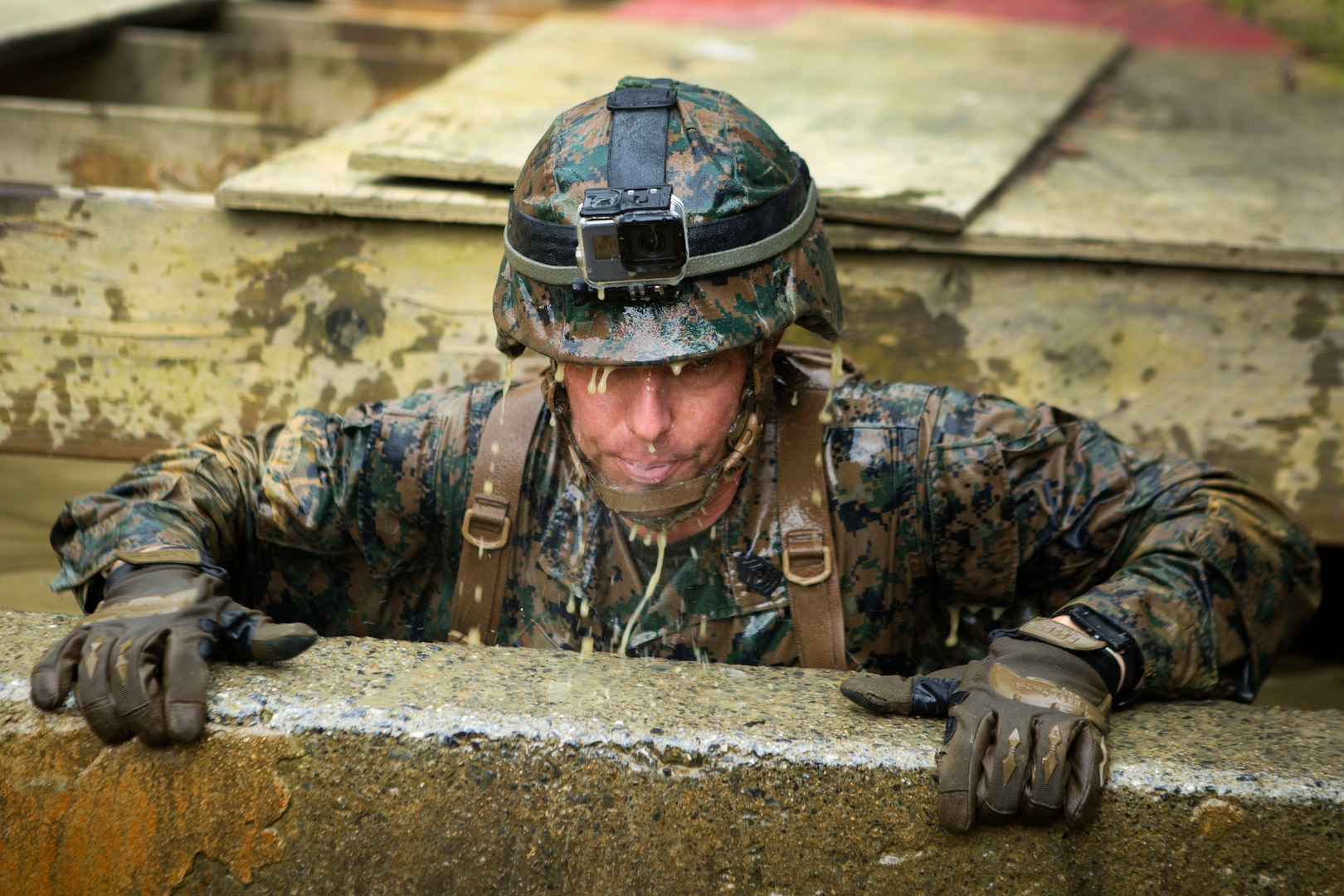 Marine Corps 1st Sgt. Thomas W. Tabisz lifts himself out of a muddy, water-filled pit during the Endurance Course.