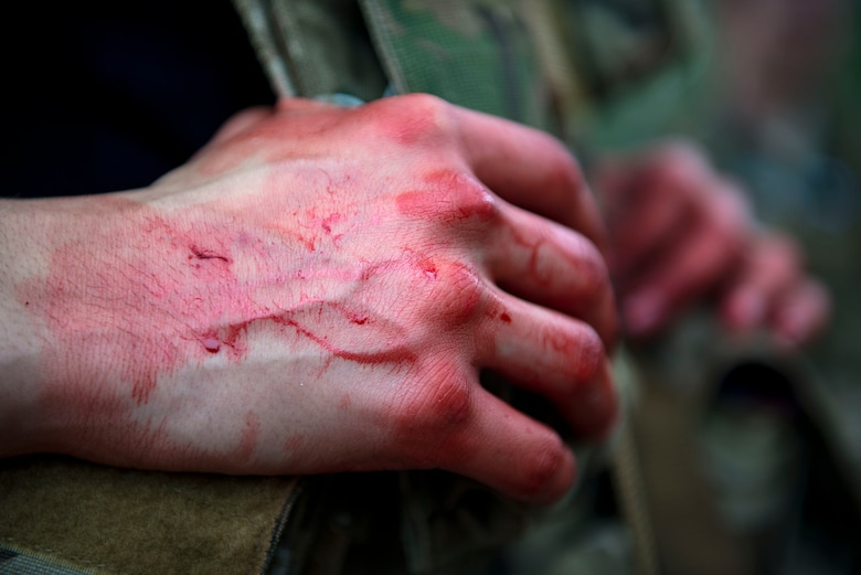 Fake blood rests on the hands of Airman 1st Class Andruw Reyes, 23d Maintenance Squadron nondestructive inspection technician, during a Tactical Combat Casualty Care course at Moody Air Force Base, Ga., Feb. 14, 2018. The training is designed to teach Airmen how to apply critical life-saving skills while engaged in a combat environment. (U.S. Air Force photo by Airman 1st Class Erick Requadt)