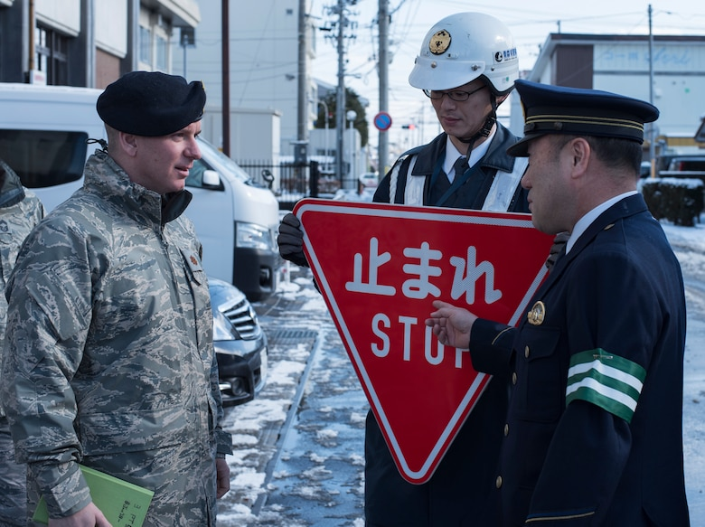 U.S. Air Force Maj. Patrick C. Gordon, left, the 35th Security Forces Squadron commander, a Misawa City Police officer, center, and Nobuhiro Izumida, right, the Misawa City Police Station Chief, engage in conversation prior to installing the first bi-lingual stop sign at an intersection in Misawa City, Japan, Feb. 15, 2018. The bi-lingual stop signs may assist guests traveling here for the 2020 Olympics in Tokyo. (U.S. Air Force photo by Airman 1st Class Collette Brooks)